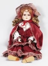 A GOOD GERMAN BISQUE HEADED DOLL wearing a velvet cloak.