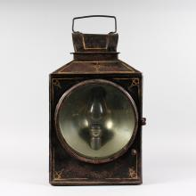 A LARGE BLACK JAPANNED RAILWAY LANTERN with carrying handle, large circular glass fronted door, the glass panel 12ins diameter, 26ins high including handle.