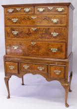 AN EARLY 18TH CENTURY WALNUT CHEST ON STAND, the upper section with a veneered and crossbanded top, moulded cornice, over two short and three graduated long drawers with feather-banded decoration, the later stand with a central drawer and flanked by deep drawers, on cabriole legs. <br>4ft 9ins high x 3ft 3ins wide x 1ft 11ins deep.