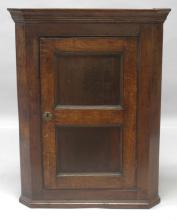 AN 18TH CENTURY OAK HANGING CORNER CUPBOARD, with a moulded cornice over a panelled door enclosing two shelves. <br>3ft 3ins high x 2ft 6ins wide.