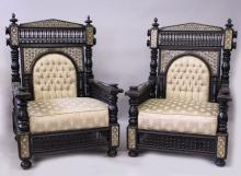 A GOOD PAIR MOORISH EBONISED AND MOTHER-OF-PEARL INLAID ARMCHAIRS, with pierced mashrabiya work panels, button upholstered back, overstuffed seat on bun feet.