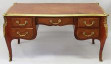 A 19TH CENTURY DESIGN FRENCH KINGWOOD AND ORMOLU WRITING TABLE, of serpentine outline, with leather inset writing surface, central frieze drawer flanked by two small drawers to each side, on cabriole legs. <br>4ft 8ins long x 2ft 6ins deep x 2ft 5ins high.