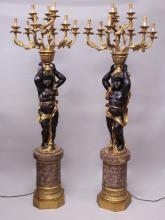 A PAIR OF BLACKAMOOR FLOOR STANDING CANDELABRA, the figures holding aloft an urn with nine scrolling branches, standing on a faux marble base. <br>6ft 2ins high.