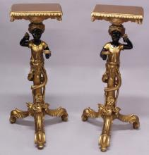 A PAIR OF BLACKAMOOR TORCHERES, the figures holding a dish and grapes in their hands, standing on a scrolling tripod base. <br>3ft 0ins high.