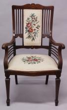 AN EDWARDIAN MAHOGANY ARMCHAIR, with inlaid cresting rail, needlework upholstered back and seat, on tapering square legs with spade feet.