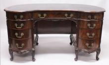 A VERY GOOD  MAHOGANY KIDNEY SHAPE DESK, early 20th Century, with gilt tooled black leather writing surface above a central frieze drawer, with four bowfront drawers to each pedestal, all with ornate cast brass handles supported on curved legs with scroll feet. <br>4ft 8ins wide x 2ft 0ins deep x 2ft 6ins high.