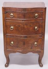 AN 18TH CENTURY CONTINENTAL WALNUT SERPENTINE CHEST, with three graduated long drawers, all with brass ring handles, on cabriole legs. <br>1ft 8ins wide x 1ft 5ins deep x 2ft 7ins high.
