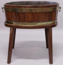 A GEORGE III MAHOGANY AND BRASS BOUND WINE COOLER, of oval form, with brass ring handles, on a later stand. <br>2ft 0ins deep x 1ft 6ins wide x 2ft 0ins high.