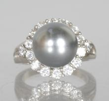 A BLACK PEARL AND BRILLIANT SET RING in silver.