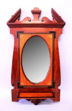 AN EDWARDIAN MAHOGANY FRAMED OVAL MIRROR with bevelled edge, broken arched pediment and small shelf. <br>2'10