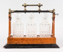 A THREE BOTTLE CUT GLASS TANTALUS in a mahogany carrying case.
