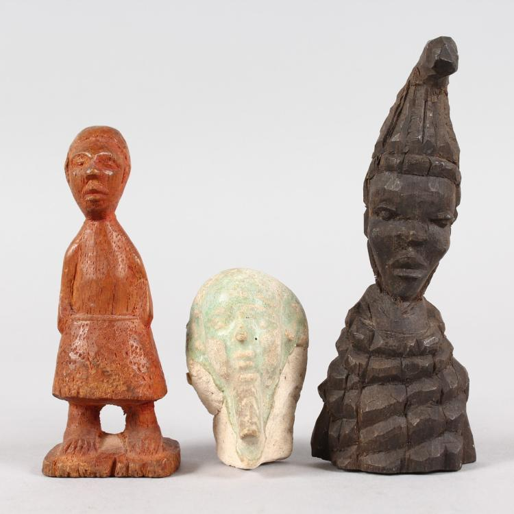 An ancient egyptian carved stone head and two wooden