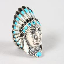 A SILVER INDIAN HEAD RING decorated with turquoise and enamel.