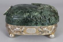A GOOD EARLY 20TH CENTURY CHINESE SILVER & JADE OVAL BOX BY LUENWO OF SHANGHAI, the fruit form jade cover carved in relief with leafage and a butterfly, the silver box with two confronting dragon in relief divided by an engraved monogram cartouche, the base with an impressed character mark and 'LUENWO', 6.2in wide x 4.25in x 3.4in high.