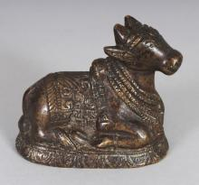 A SMALL 19TH CENTURY INDIAN BRONZE OF SHIVA'S NANDI BULL, 3in long & 2.5in high.