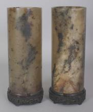 A PAIR OF EARLY 20TH CENTURY CHINESE JADE CYLINDRICAL VASES, each supported on a fixed carved wood stand, the predominantly dark green stone with white, russet and black inclusions, 9.25in high overall, the vases themselves 7.9in high.