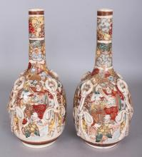 A PAIR OF EARLY 20TH CENTURY JAPANESE SATSUMA STYLE EARTHENWARE BOTTLE VASES, the sides moulded with tassels, 10.6in high.