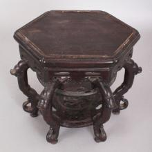 A GOOD QUALITY CHINESE HEXAGONAL SECTION CARVED HARDWOOD STAND, with pierced frieze and undertier, 10.4in wide at widest point, the top surface 9.4in wide at widest point, the stand 8.3in high.