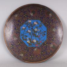 A GOOD QUALITY JAPANESE MEIJI PERIOD CLOISONNE DISH, decorated to its centre with a sky-blue ground foliate hexagonal foliate panel, 12in diameter.