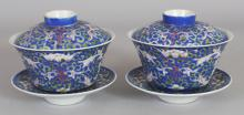 A PAIR OF 19TH/20TH CENTURY CHINESE BLUE GROUND LOTUS DECORATED PORCELAIN TEABOWLS, COVERS & STANDS, the bases of the bowls each with a six-character Guangxu mark, 3.3in high overall on stands, the teabowls themselves 4.1in diameter & 2.25in high. (6 pieces).