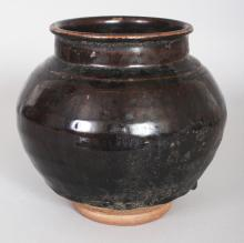 A CHINESE MING DYNASTY BROWN GLAZED STONEWARE STORAGE JAR, the glaze falling well short of the foot, 6.6in wide at widest point & 6.1in high.