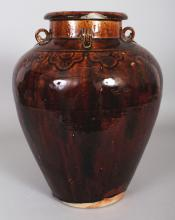 A CHINESE MING DYNASTY MATABAN BROWN GLAZED CERAMIC STORAGE JAR, the shoulders with four lug handles, the base unglazed, 12.3in high.