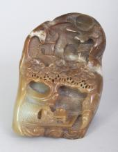 A CHINESE BROWN JADE BOULDER, carved in deep relief with a river boat beneath pine and beneath a moon shrouded settlement, 3.7in wide at widest point & 5.25in high.