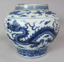 A LARGE CHINESE MING STYLE BLUE & WHITE PORCELAIN DRAGON JAR, the base unglazed, 14.25in wide at widest point & 13in high.