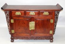 A GOOD CHINESE HARDWOOD ALTAR TABLE, with three drawers above a pair of cupboard doors, 54.5in wide x 18.25in deep x 35in high.