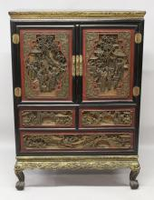 AN EARLY 20TH CENTURY CHINESE CARVED GILT WOOD CABINET, with two doors opening above two short drawers and a long drawer, the sides, doors and drawers carved in deep relief with figural terrace and landscape scenes, 36in wide x 17.5in deep x 51.8in high.