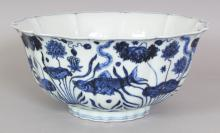 A CHINESE MING STYLE PETAL LOBED PORCELAIN BOWL, decorated with fish swimming in a lotus pond, the base with a six-character Xuande mark, 8.9in diameter & 4.2in high.