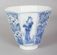 A 19TH CENTURY JAPANESE ARITA PORCELAIN BEAKER CUP, of flaring octagonal form, the sides painted with alternating figural and floral panels, the base with a maker's mark, 3.5in wide & 3.1in high.