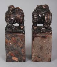 A PAIR OF CHINESE HARDSTONE SEALS, each surmounted by an elephant and boy rider, 3in high.