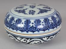 A CHINESE MING STYLE TIBETAN MARKET BLUE & WHITE CIRCULAR PORCELAIN BOX & COVER, the cover decorated with Tibetan characters and cloud scrolls, the base with an archaic four-character mark, 5.3in diameter & 3.2in high overall.