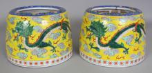 A PAIR OF EARLY 20TH CENTURY ORIENTAL YELLOW GROUND PORCELAIN DRAGON JARS, with sloping sides and curved rim, each base unglazed, 8.4in diameter at base & 5.75in high.