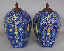 A PAIR OF 19TH CENTURY BLUE GROUND '100 ANTIQUES' FAMILLE ROSE HEXAGONAL SECTION MOULDED PORCELAIN JARS, with fitted wood covers, 14.5in high overall to tops of finials, the jars themselves 12in high.