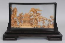 A 20TH CENTURY CHINESE CORK CARVING, in a wood and glass frame supported on a fitted rectangular wood stand, the cork carved with a detailed scene of a dwelling with terrace, rockwork and overhanging pine, 12.6in wide x 3in deep x 7.8in high.
