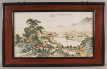 A CHINESE REPUBLIC STYLE WOOD FRAMED PORCELAIN PLAQUE, decorated with calligraphy and with an extensive mountainous river landscape setting, the frame 27in x 17in, the visible area of the plaque itself 20.75in x 11.8in.