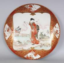A GOOD QUALITY LATE 19TH CENTURY JAPANESE KUTANI PORCELAIN DISH, painted with a bijin on geta crossing a small bridge, the base with a maker's mark, 14.7in diameter.