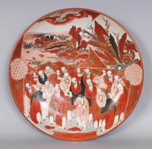 ANOTHER JAPANESE KUTANI PORCELAIN DISH, circa 1900, painted with a panel of conversing Sennin, the base with a Kutani mark, 14.3in diameter.