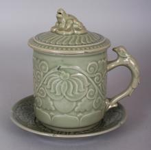 A KOREAN CELADON PORCELAIN TANKARD & COVER WITH MATCHING STAND, the tankard and stand each with an impressed seal mark, the tankard 5.75in high overall, the stand 6in diameter.