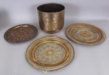 A 20TH CENTURY CAIRO WARE SILVER-METAL & COPPER INLAID BRASS DISH, 12.75in diameter; a deep Islamic brass bowl, 9.6in diameter at rim & 9.1in high; and a pair of Indian embossed brass dishes, 14in diameter. (4)