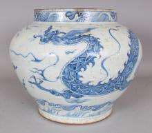 A CHINESE YUAN STYLE BLUE & WHITE PORCELAIN DRAGON JAR, the base unglazed, 12.9in wide at widest point & 10.4in high.