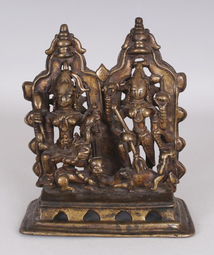 An Unusual Bronze Group Depicting Ambika and Durga, Western India, 14th/15th Century, on arcaded rectangular base, each with four arms and an arched prabha behind surmounted by a kalasa, the former seated on her lion, clasping her child on her left knee, her other hands holding various attributes, the latter depicted slaying the buffalo demon (Mahisasuramardini), wielding a sword, shield and trident, 18cm (7 1/8in) high.Provenance: Collection of the Late Andrew Solomon, London, inv. no. A79. Purchased from Sotheby's London, 11 July 1972, lot 52. The original invoice is sold with this lot.Ambika and Durga are, with the other goddess Kali and Parvati, associated with the shakta cult, which flourished from the 9th century, focusing on divine female energy (Dictionary of Hindu Lore and Legend, Anna Dallapiccola, London 2002, pp.23 & 173).
