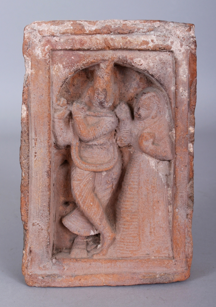 A Small Terracotta Architectural Relief, Bengal, Eastern India, circa 18th century, of rectangular form, depicting Radha and Krishna in relief, within an arched niche, the Hindu god playing his flute, watched by his companion, 15.2cm (6in) x 9.7cm (3 3/4in) x 3.5cm (1 3/8in).Provenance: Collection of the Late Andrew Solomon, London, inv. no. A24. Purchased on Portobello Road, 19 July 1969