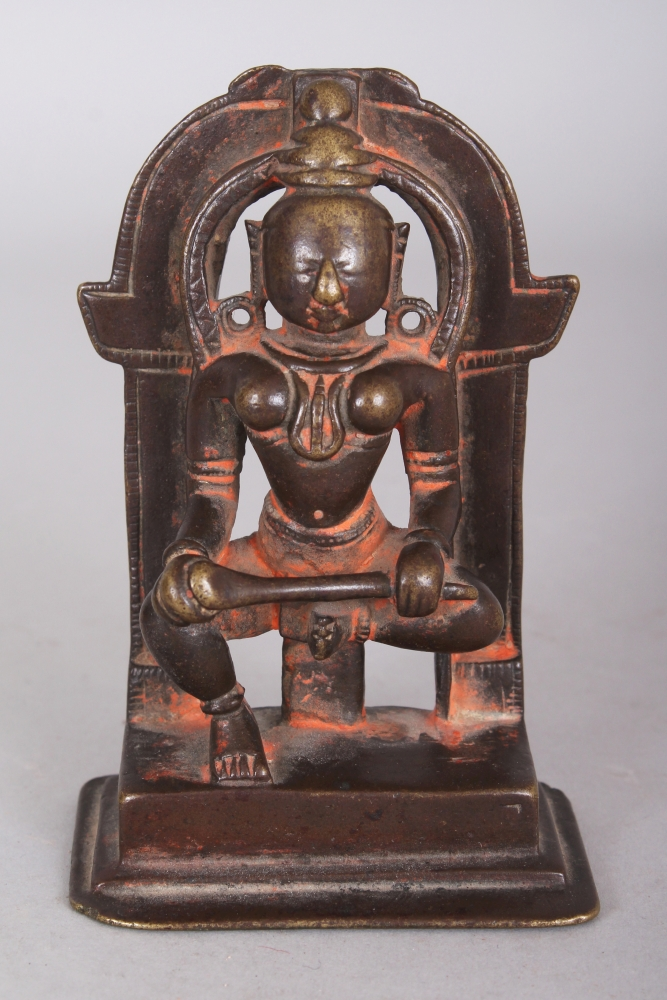 A Bronze Shrine Depicting Annapurna, Western India, 15th/16th century, the female deity seated in lalitasana, holding her ladle across her lap, surrounded by an arched prabha, kalasa now missing, 9.8cm (3 7/8in) high.Provenance: Collection of the Late Andrew Solomon, London, inv. no. A72. Purchased from Obelisk Gallery (J. G. McMullen), 15 Crawford Street, London W1, 29 December 1971.Annapurna is a form of Parvati, consort of Siva. She feeds the starving by ladling out rice from her bowl.