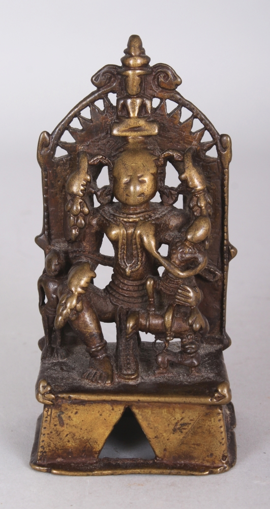 A Jain Bronze Shrine Depicting Ambika, Western India, dated samvat 1522/1465 AD, the four armed goddess seated on a raised platform, with triangular openings, holding her child on her left knee, her other three hands holding leafy branches, a pierced aureole behind, with kalasa and jina above, inscribed dedication and date on the reverse in devanagari script, 11.5cm (4 1/2in).Provenance: Collection of the Late Andrew Solomon, London, inv. no. A46. Purchased Alain Presencer, 26 September 1970.