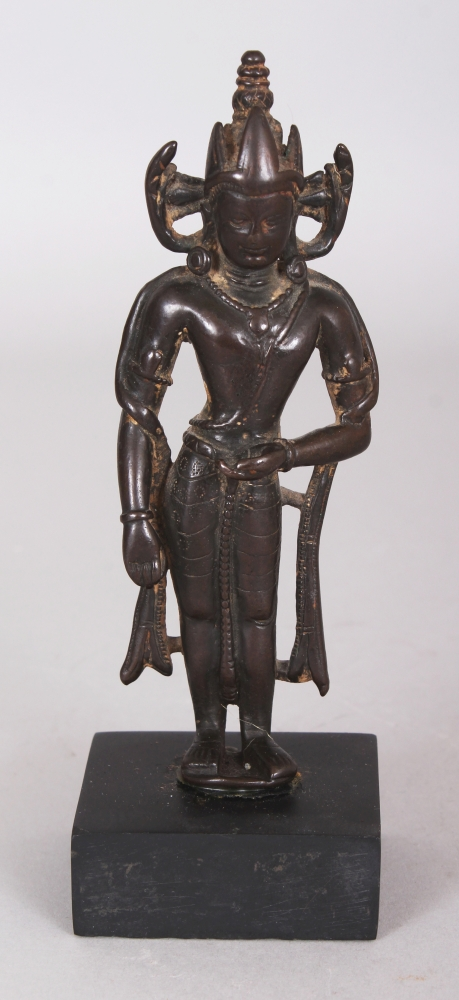 A Small Bronze Crowned Figure of Buddha, Kashmir, 11th/12th century, the slender figure standing with body slightly flexed, his hands in bhumisparsa and dhyana mudra, wearing earrings and three-leafed crown, mounted, 12cm (4 3/4in).Provenance: Collection of the Late Andrew Solomon, London, inv. no. A1. Purchased from Oriental Antiquities Ltd., 21 Barrett Street, London W1, 25 March 1969. The original invoice is sold with this lot.
