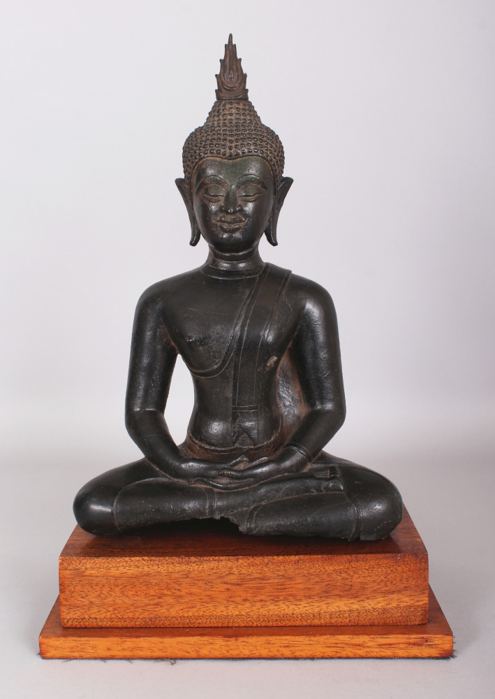 A Bronze Figure of Buddha, Chen Sen Style, Northern Thailand, circa 15th century, seated in sattvasana, his hands in dhyana mudra, with elongated earlobes and separately cast flame usnisa, later wood stand, 33cm (13in) high.Provenance: Collection of the Late Andrew Solomon, London, inv. no. A34. Purchased from Obelisk Gallery, (J. G. McMullen), 15 Crawford Street, London W1. 22 October 1969.