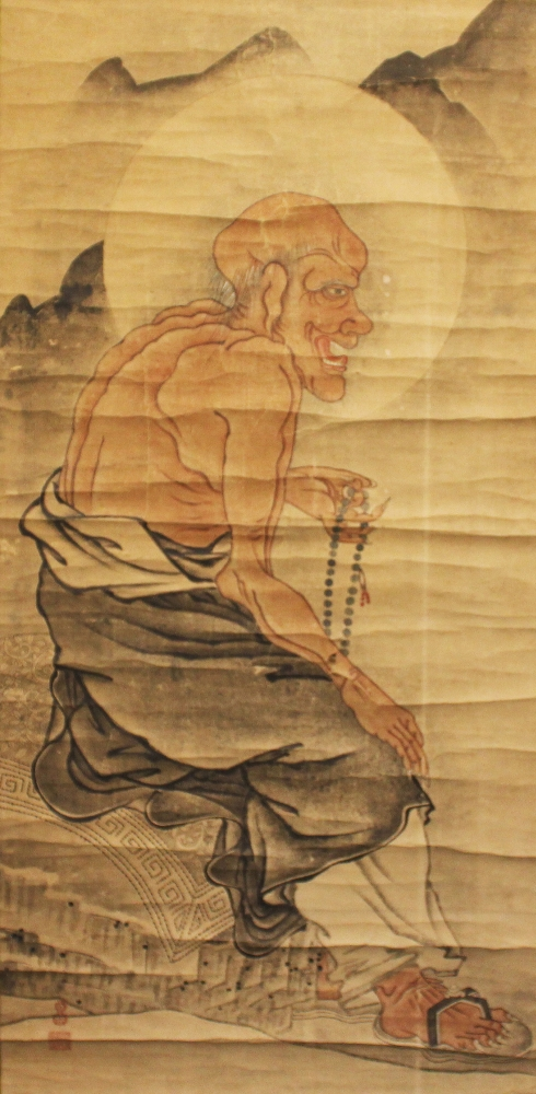 A SIGNED ORIENTAL SCROLL PAINTING ON PAPER, depicting a seated sage clasping prayer beads, the painting itself approx. 43in x 21in.